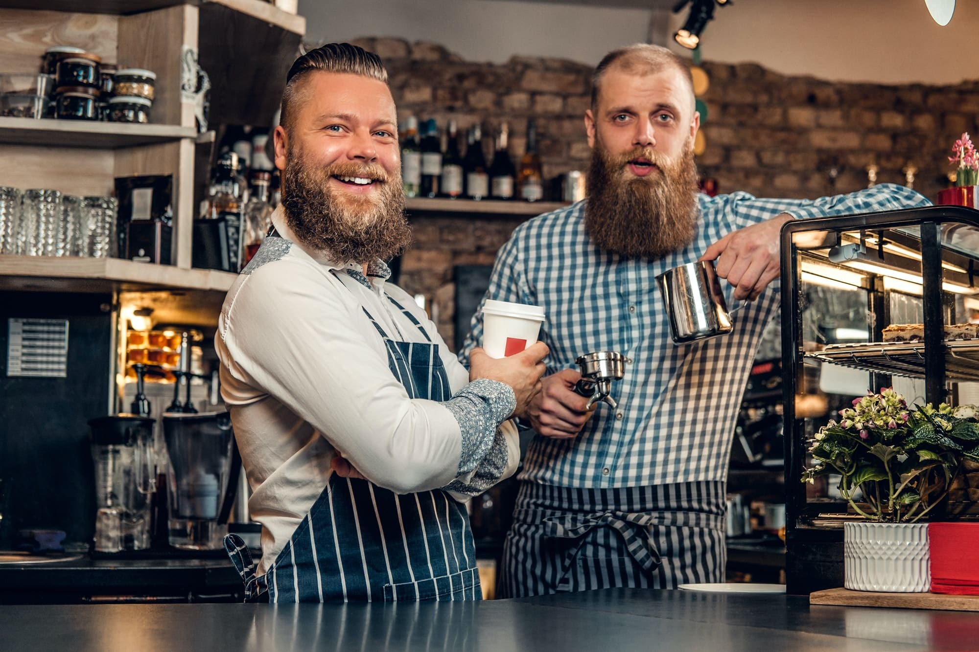 Two bearded hipster coffee shop owners at the counter.
